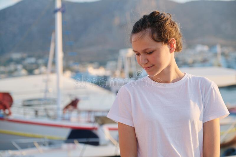 Portrait of teenage girl 15 years old, happy smiling teenager. Summer sunset sea harbor with yachts background. Vacation, adolescence, travel concept stock image