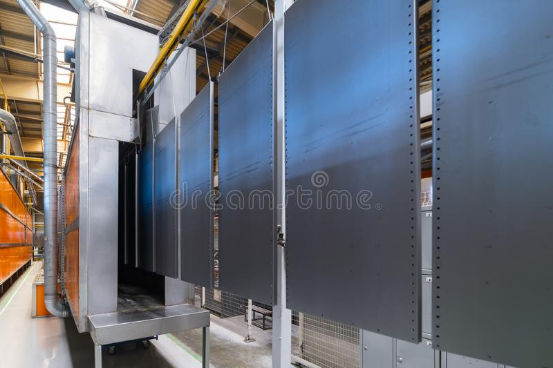 Powder coating line. Metal panels are suspended on an overhead conveyor line. stock image