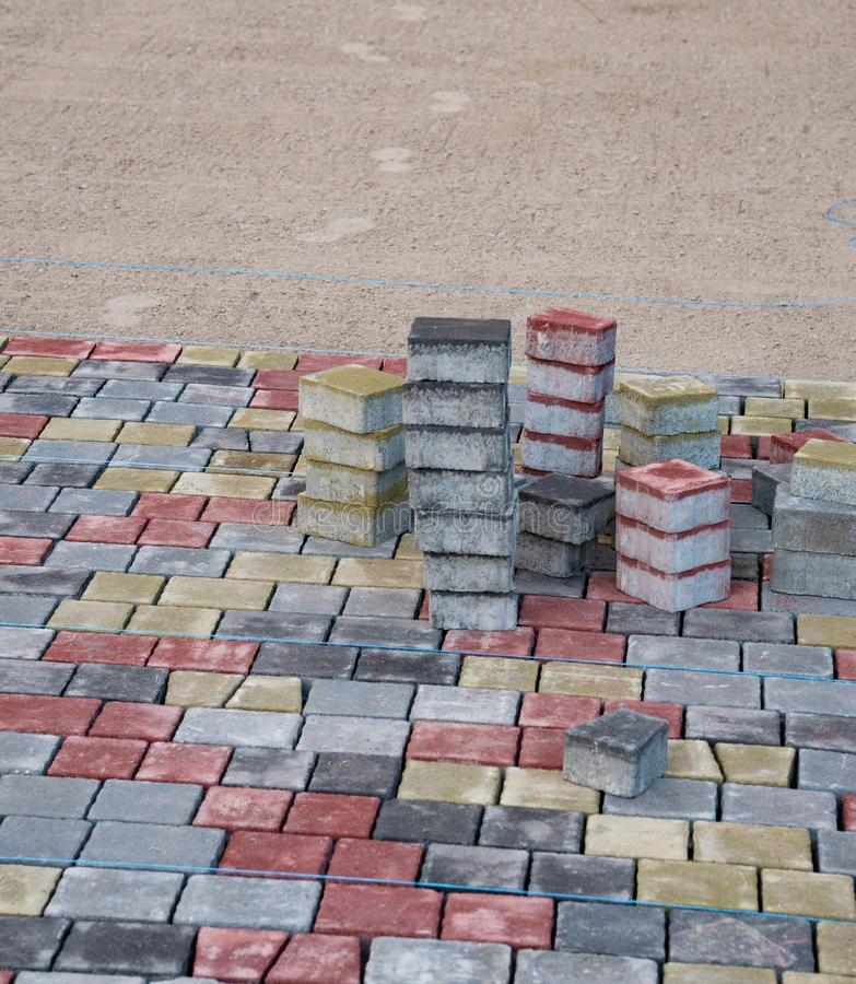 Preparation for laying paving slabs on the gravel substrate. Sorted colored pavement tiles lined up in towers. Beauty in everyday. Work royalty free stock image