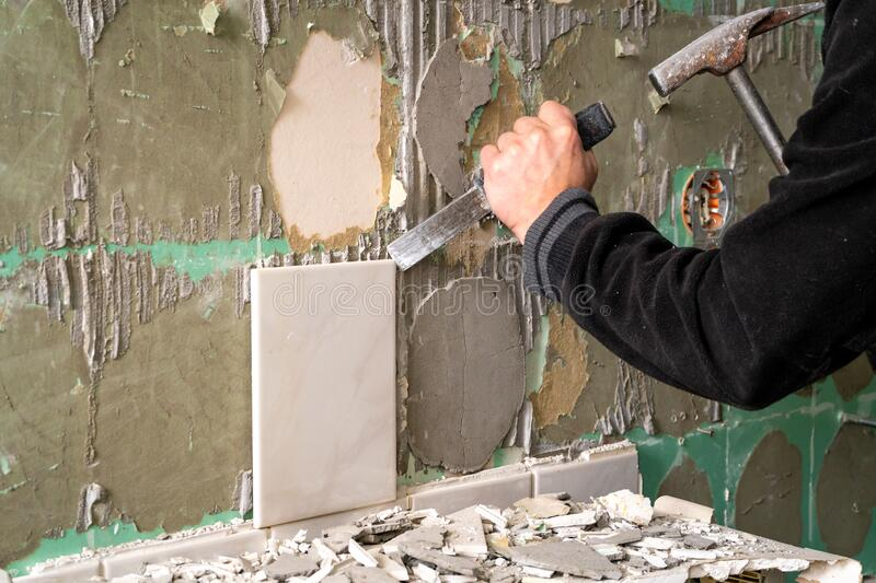 Preparation of repair the bathroom. Man Removing old tiles.  stock photos