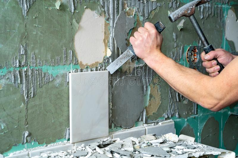 Preparation of repair the bathroom. Man Removing old tiles.  royalty free stock images
