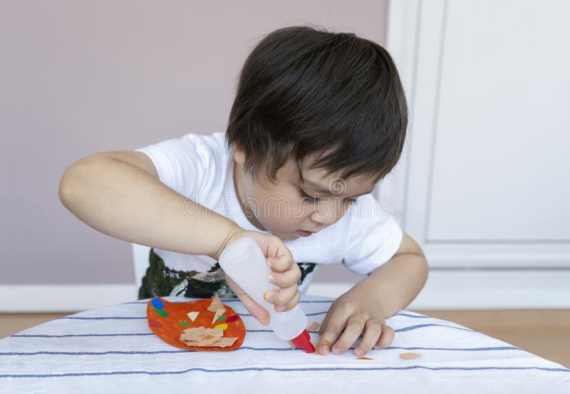 Preschool kid putting glue stick on paper for his school homework, Cute little boy using colour paper making easter eggs for DIY stock image