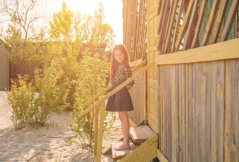 Pretty little girl on stairs of wooden house. Pretty little barefoot girl on stairs of wooden house at a seaside in sunlight stock images