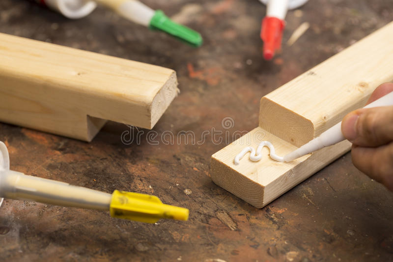 Putting glue on a piece of wood royalty free stock photography