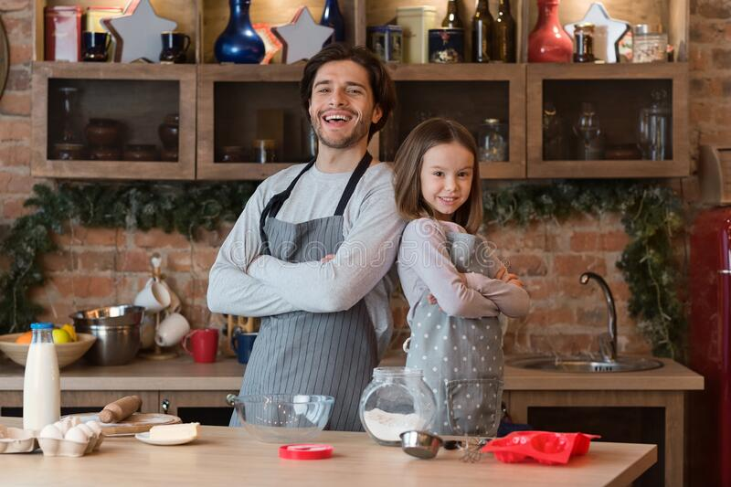 Ready For Baking. Dad And Little Daughter Posing In Kitchen Wearing Aprons royalty free stock photos