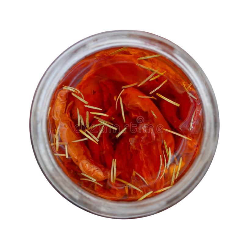 Red homemade oven dried tomatoes with rosemary stuffed with olive oil in a glass jar, top view, close-up, isolated stock photography