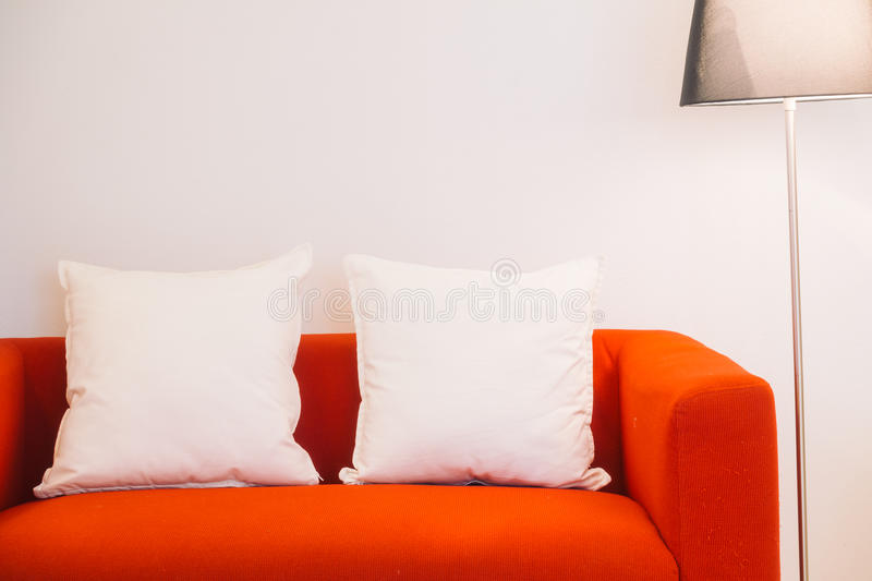 Red sofa with pillow and light lamp. Decoration in living room interior - Vintage Light Filter stock photography