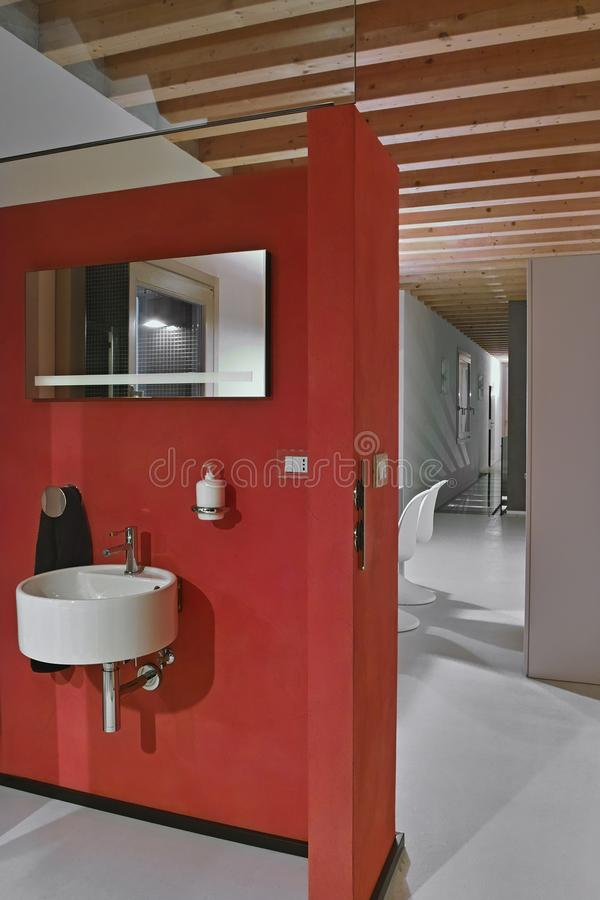 Red wall behind whic there is a round wall-mounted washbasin and royalty free stock photos