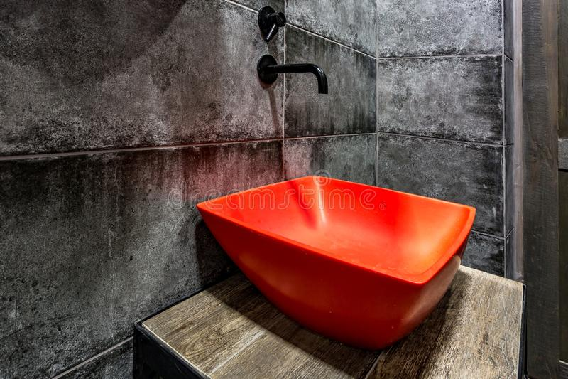 Red washbasin with faucet in expensive loft bathroom in elite sport bar on black brick wall background.  royalty free stock images