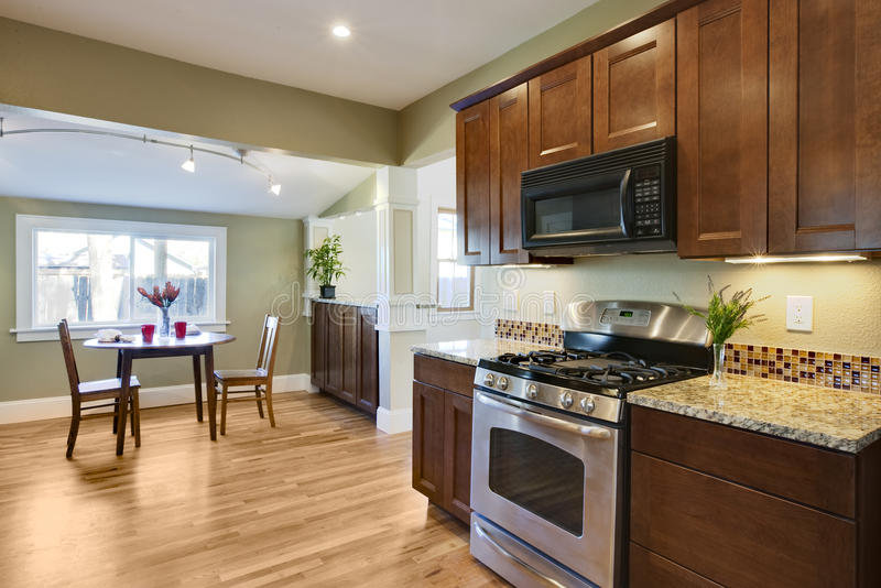 Remodel kitchen with wood flooring. Remodel kitchen with oven, granite counters, and reflective wood floor royalty free stock photography