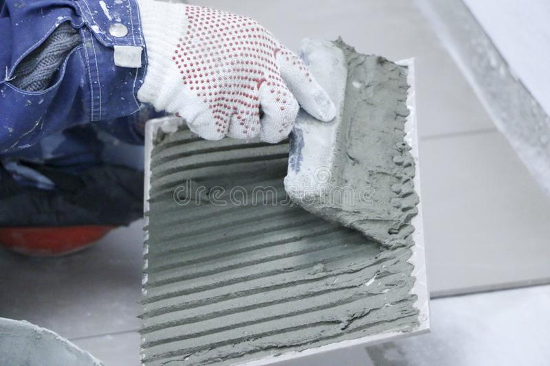 Repair - interior decoration. Laying of floor ceramic tiles. Men`s hands tiler in gloves with spatula spread cement mortar on royalty free stock photography