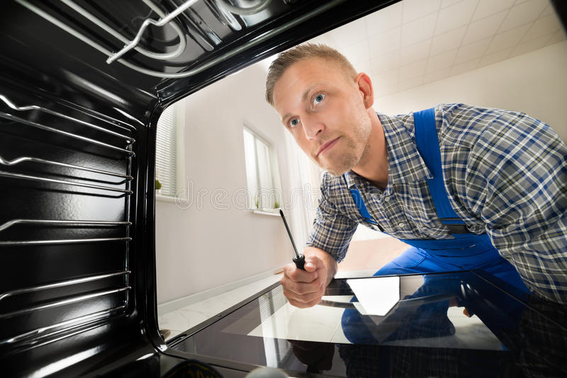 Repairman Fixing Kitchen Oven. Young Repairman With Screwdriver Fixing Kitchen Oven stock photos