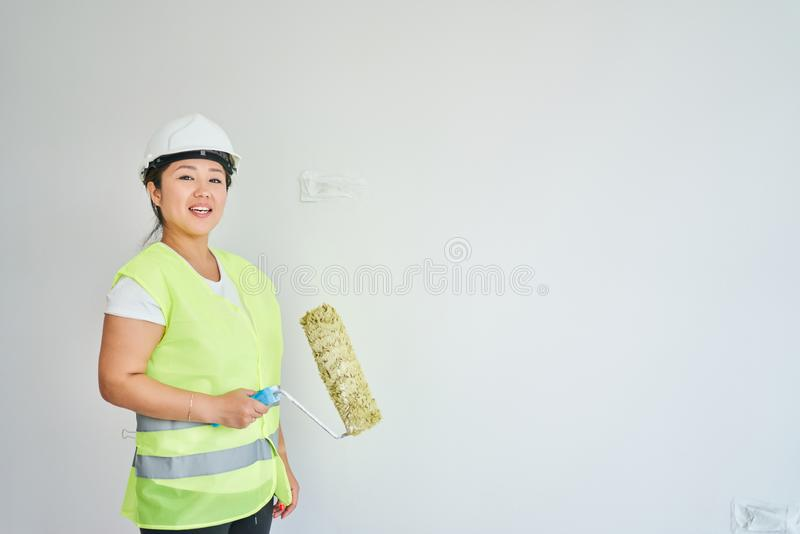 Repairs in the apartment, a girl in a green vest and a white helmet is in a white room with a roller in his hands royalty free stock photo