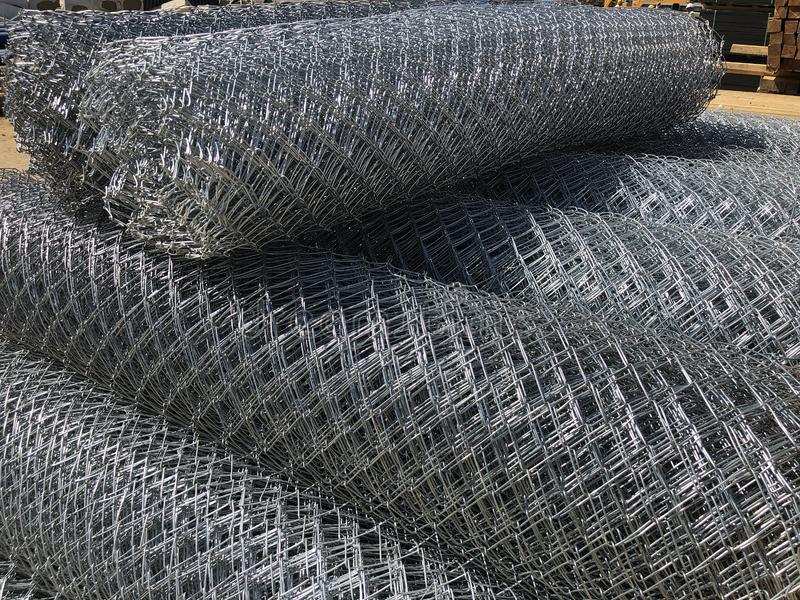 Rolled chain-link fence. Metal mesh netting rolled into rolls.  royalty free stock photos