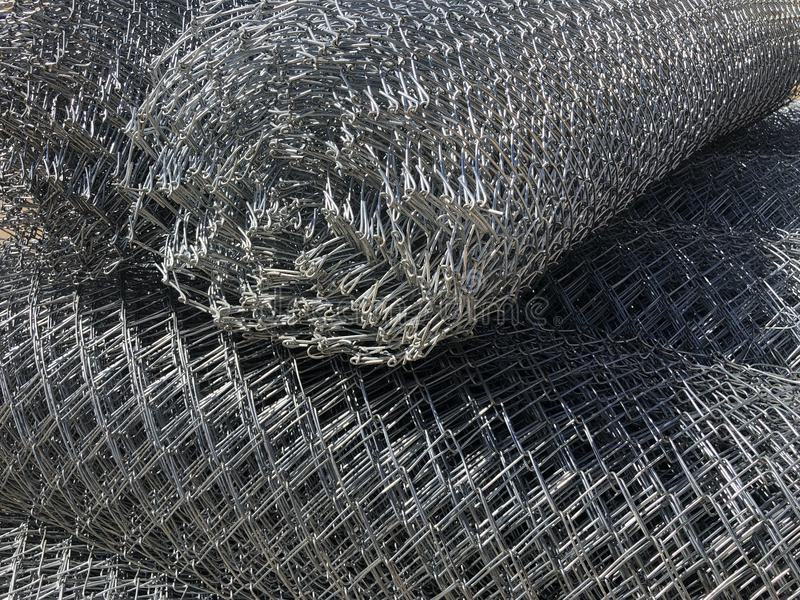 Rolled chain-link fence. Metal mesh netting rolled into rolls.  royalty free stock photo