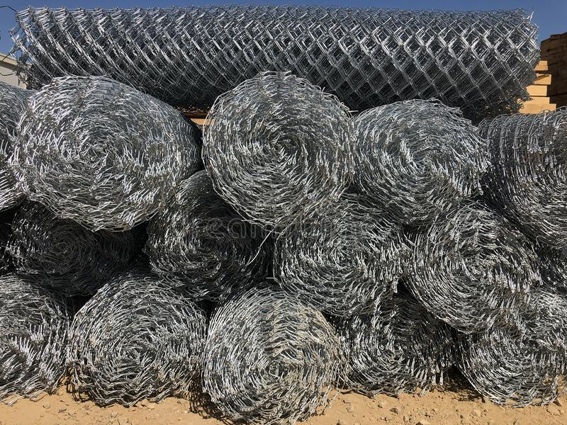 Rolled chain-link fence. Metal mesh netting rolled into rolls.  royalty free stock images