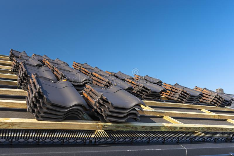 Roof ceramic tile arranged in packets on the roof on roof battens. Preparation for laying roof tiles. Roof ceramic tile arranged in packets on the roof on roof stock image