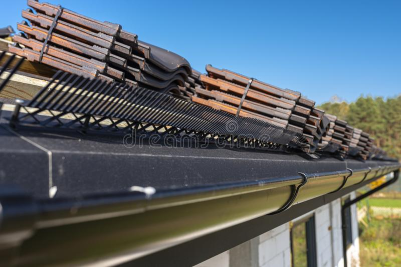 Roof ceramic tile arranged in packets on the roof on roof battens. Preparation for laying roof tiles. Roof ceramic tile arranged in packets on the roof on roof royalty free stock images