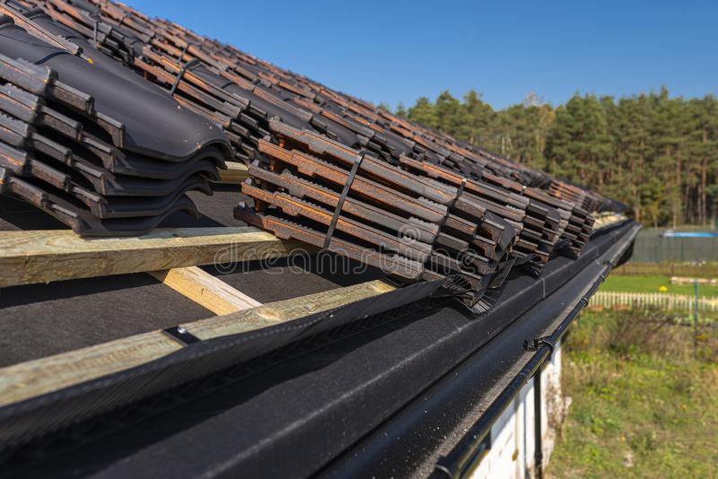 Roof ceramic tile arranged in packets on the roof on roof battens. Preparation for laying roof tiles. Roof ceramic tile arranged in packets on the roof on roof royalty free stock image