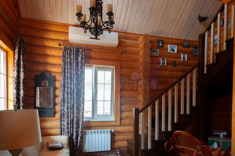 Rustic house, log cabin inside, wooden staircase to the second floor, light from the Windows royalty free stock image