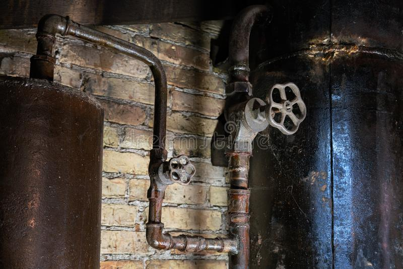 Rusty boiler room pipes. Old metal boiler generating heating and delivering it to home through pipeline. Hot water or gas is being. Delivered with this system stock images