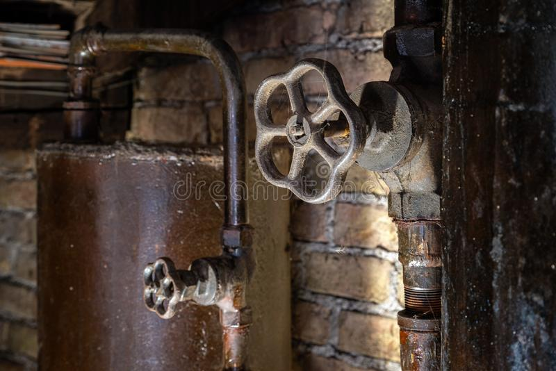 Rusty boiler room pipes. Old metal boiler generating heating and delivering it to home through pipeline. Hot water or gas is being. Delivered with this system royalty free stock image