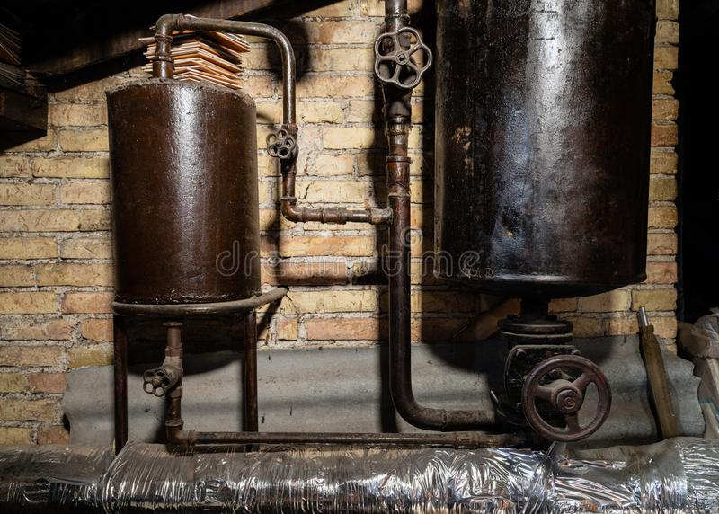 Rusty boiler room pipes. Old metal boiler generating heating and delivering it to home through pipeline. Hot water or gas is being. Delivered with this system royalty free stock photo