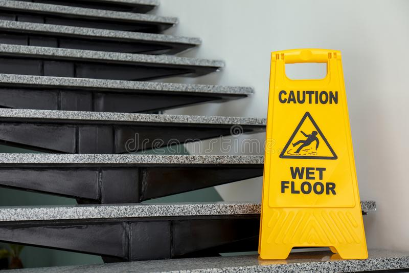 Safety sign with phrase Caution wet floor on stairs. Cleaning service stock images