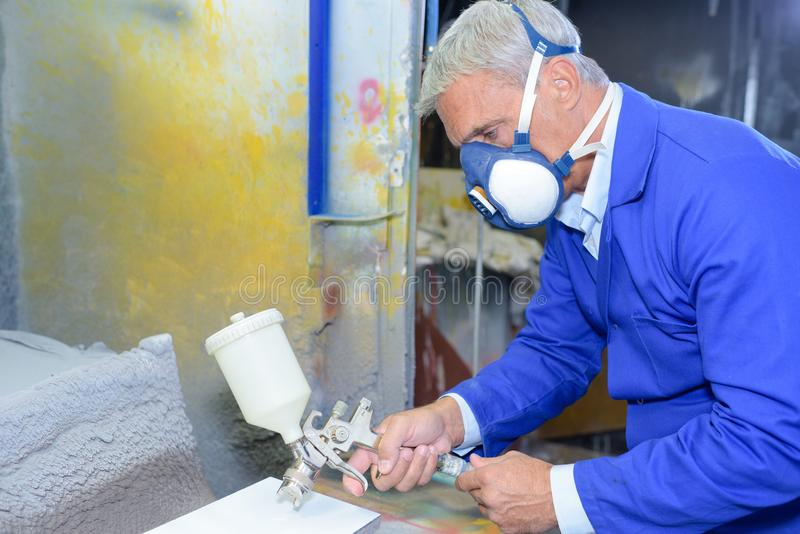 Senior painter wearing custom suit spray painting royalty free stock photos