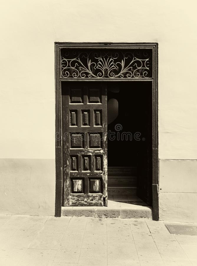Sepia image of an old wooden door with panels in a traditional spanish house half open revealing stairs inside decorative ironwo. A sepia image of an old wooden royalty free stock image