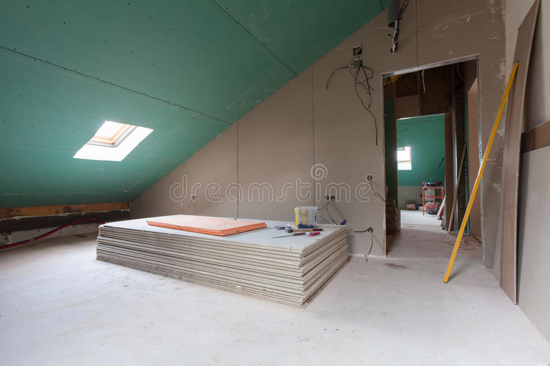 Sheets of drywall, parts of scaffolding, handle tools and construction material in the room of apartment during on the remodeling stock photos