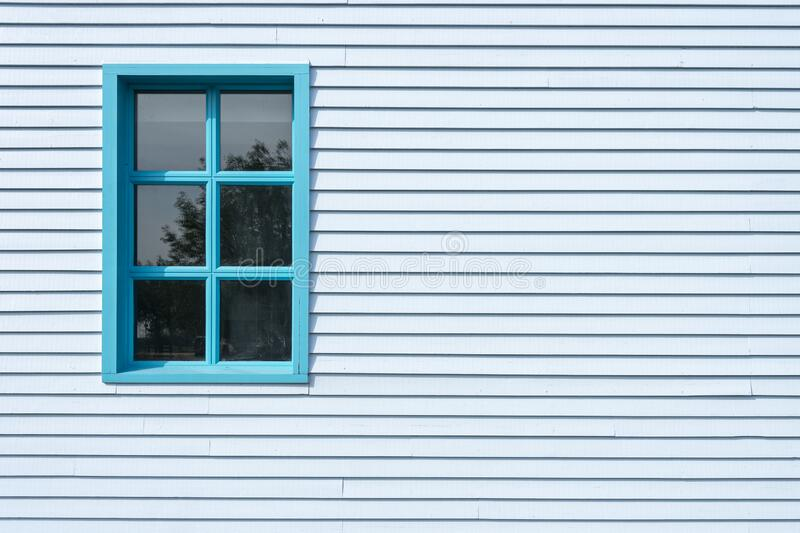 Side of a blue clapboard building. Side of a blue wooden clapboard building with a window, painted blue stock photography