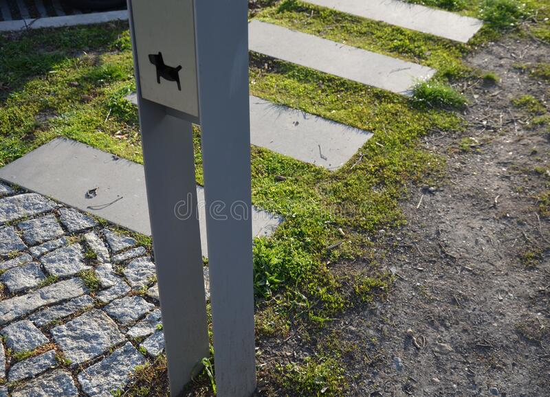 Detail of placement of dog excrement bags in a metal post symbol dog  pedal road made of concrete tiles and chipped granite around. Sign, fence, wooden, road royalty free stock photo