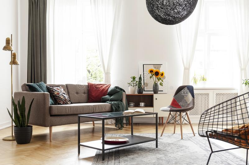 Simple brown sofa with cushions in an eclectic, white living room interior with natural light coming through big windows. Concept stock photos