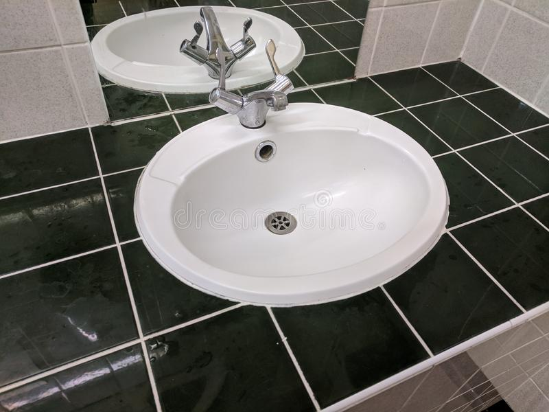 Sink with black tiling and white grouting angled. Isometric Black tiles white grouting and mirror with sink amd taps stock photos