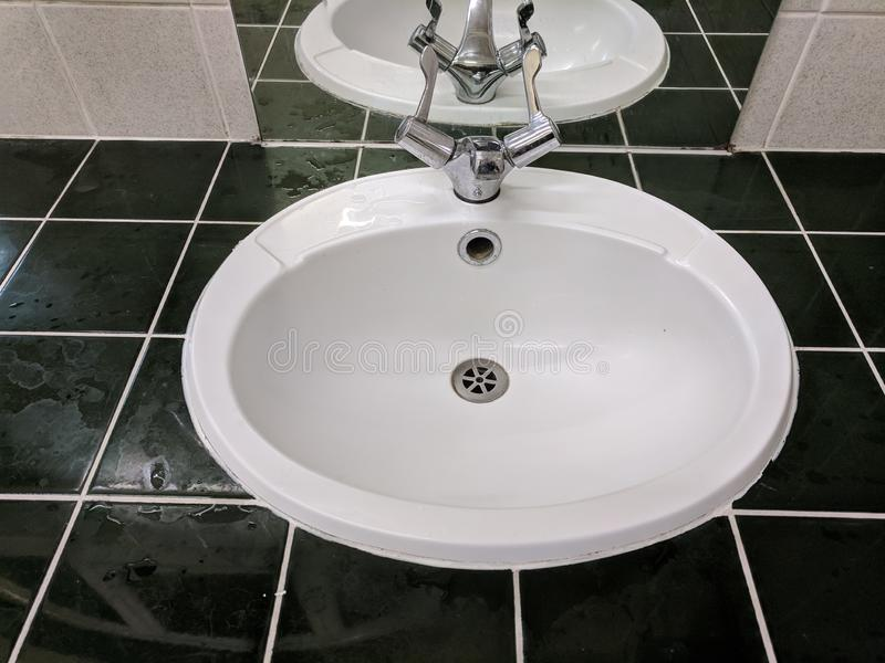 Sink with black tiling and white grouting. Black tiles white grouting and mirror with sink amd taps stock image