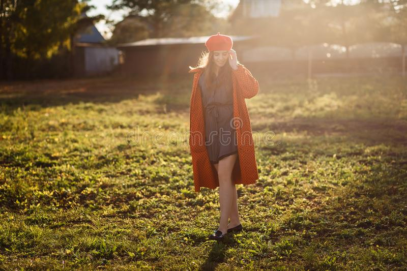 Sixteen-year-old smiling teen girl in a red beret and orange coat in direct sunlight outdoors royalty free stock photo