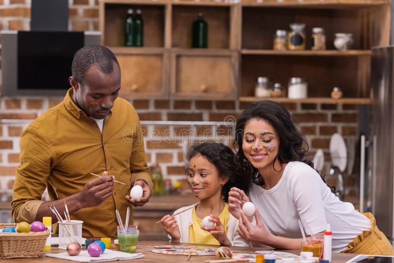 African american parents and daughter painting easter eggs together on kitchen. Smiling african american parents and daughter painting easter eggs together on royalty free stock image