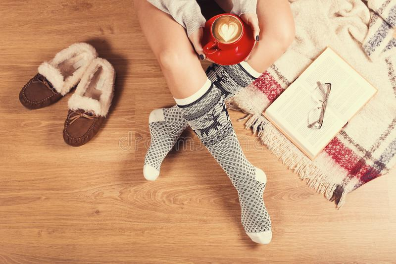 Young woman sitting on the wooden floor with cup of coffee, plaid, cookie and book. Close-up of female legs in warm socks with a stock photo