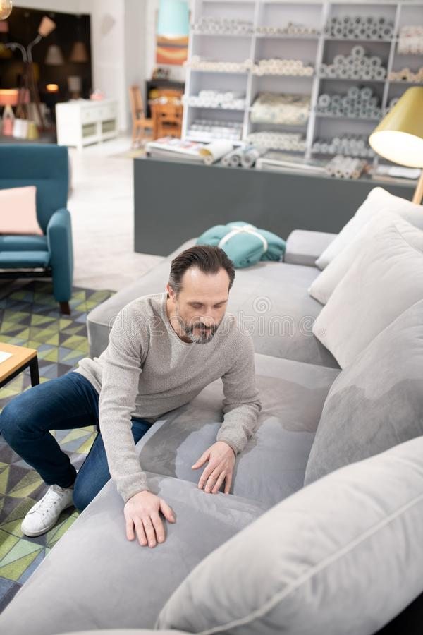 Man in light sweater and jeans touching the sofa. Soft and smooth. Man in light sweater and jeans touching the sofa stock image