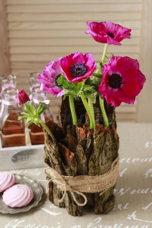 Spring table decoration with bark and anemone flowers. Party decor stock photo