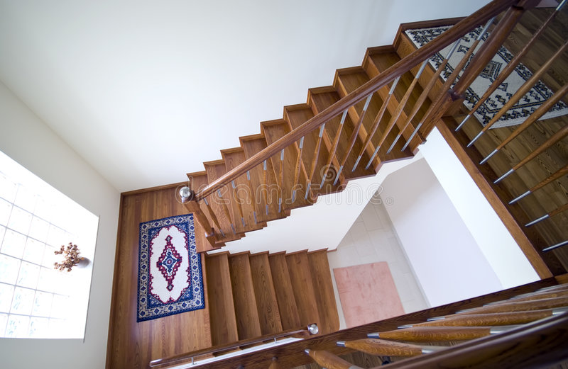 Stairs in modern house. A staircase of brown wooden stairs in a modern house royalty free stock image