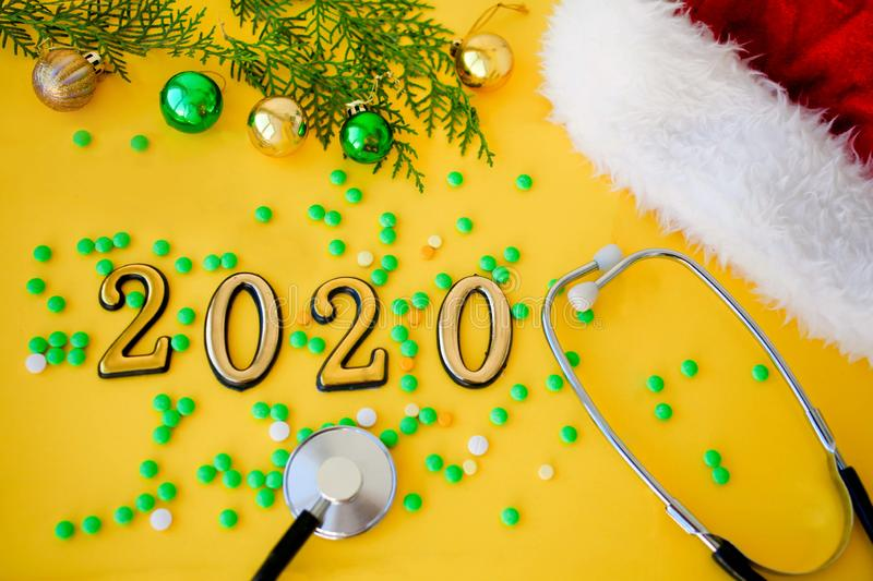 Stethoscope with 2020 number , green pills and christmas balls on yellow background. Happy New Year for health care and medical stock photos
