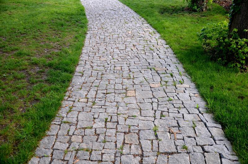 Granite paving of irregular sections of chipped stone around a park with green lawn gray color of the pedestrian path. Stone, road, cobblestone, path, pavement royalty free stock image