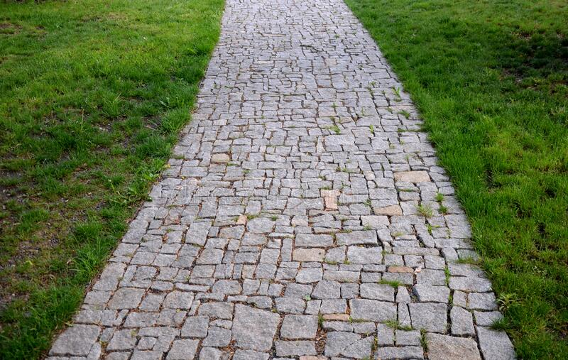Granite paving of irregular sections of chipped stone around a park with green lawn gray color of the pedestrian path. Stone, road, cobblestone, path, pavement royalty free stock photo