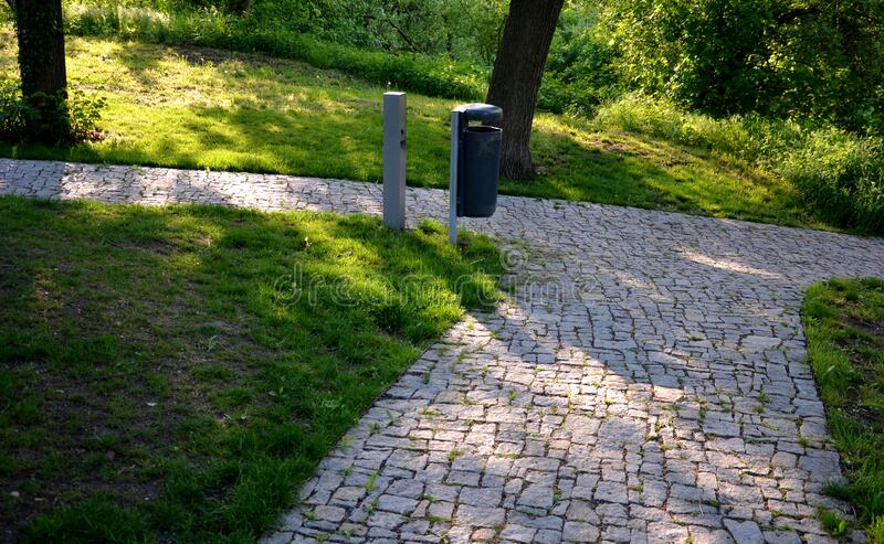 Granite paving of irregular sections of chipped stone around a park with green lawn gray color of the pedestrian path. Stone, road, garden, street, cobblestone stock photo