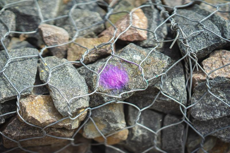 Stones in Metal mesh netting, wire. Purple spot as design. Modern background. Stones in Metal mesh netting, wire. Purple spot as design. Background for modern stock image