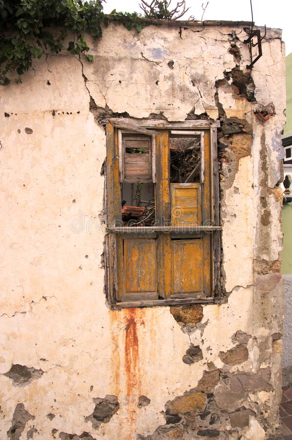 Window in an abandoned house with copy space. Street-facing window showing dilapidated condition of an old house that no one is trying to repair with copy space stock photo