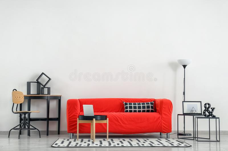 Stylish furniture with comfortable sofa near light wall royalty free stock image