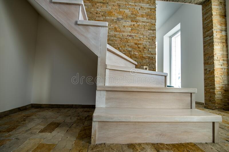 Stylish wooden contemporary staircase inside loft house interior. Modern hallway with decorative limestone brick walls and white stock image